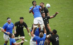 Namibia's lock Tjiuee Uanivi (C) jumps for the ball in a line out  during the match between New Zealand and Namibia.