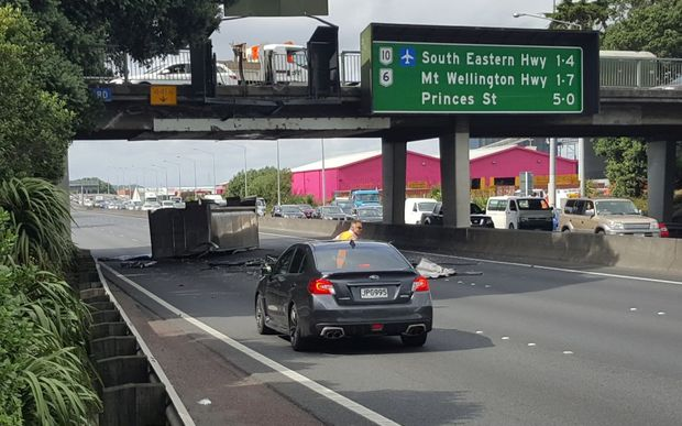 The truck flipped onto its side after hitting the Penrose overbridge on Auckland's Southern motorway.