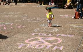 A child walks on slogans that Extinction Rebellion activists wrote in chalk at a gathering in Sydney.