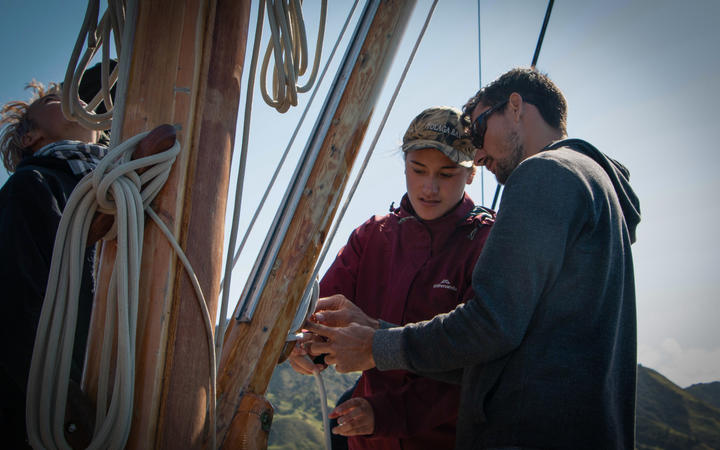 A crew member shows a trainee how to lock on.