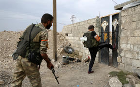 Turkey-backed Syrian fighters break open  the front door of a house at a postition that they are holding in the Syrian border town of Ras al-Ain on October 19, 2019.