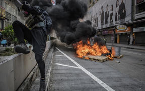 A protester jumps over a barrier after setting a fire on a road during a pro-democracy march in the Kowloon district in Hong Kong on October 20, 2019
