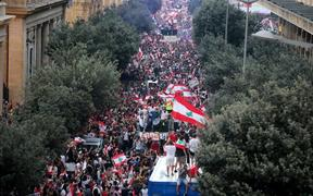 Thousands of Lebanese demonstrators wave their country's flag during a mass protest in Beirut demanding the fall of the government.