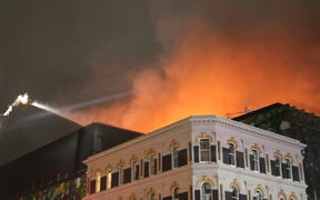 The smoke billowing from the rooftop of the SkyCity convention centre is lit up by the flames into the night. (22 October)