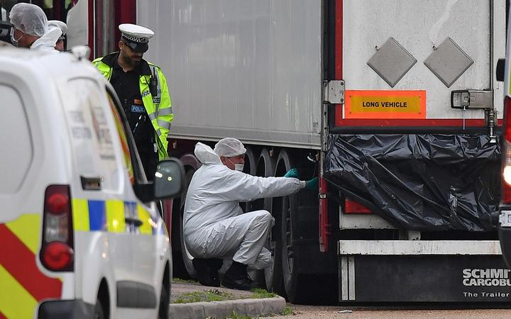 British Police forensics officers work on lorry, found to be containing 39 dead bodies, at Waterglade Industrial Park in Grays, east of London.