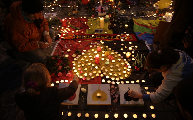People light candles in tribute to victims at a makeshift memorial in front of the stock exchange at the Place de la Bourse in Brussels on March 22, 2016.