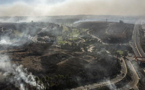 Aerial view of palms and brush burning at Real Del Mar residential outskirts Tijuana, Baja, California state.