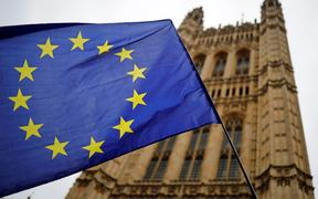 A European Union flag and belonging to an anti-Brexit activist flies outside the Houses of Parliament in London on October 23, 2019.