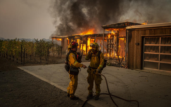 Firefighters discuss how to approach the scene as a home burns near grape vines during the Kincade fire in Healdsburg, California.