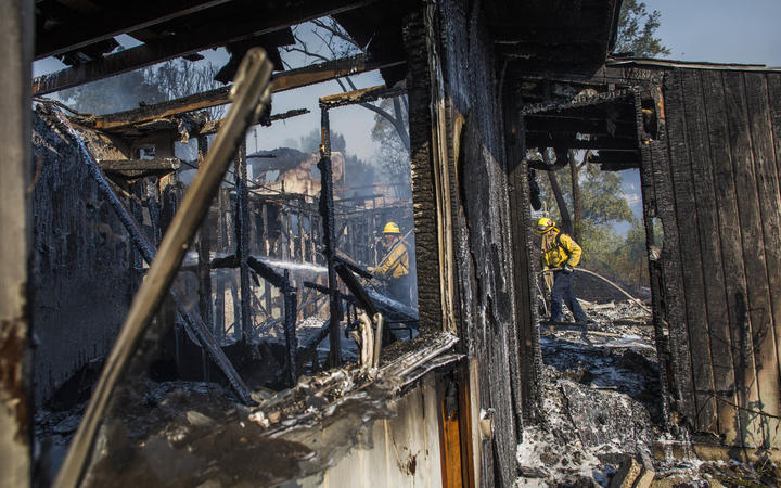 Firefighters battle the Tick Fire in houses on fire in Brentwood, California.