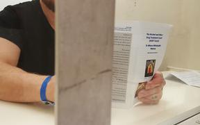 A drug court applicant in the holding cells looks over a leaflet about the court before his appearance
