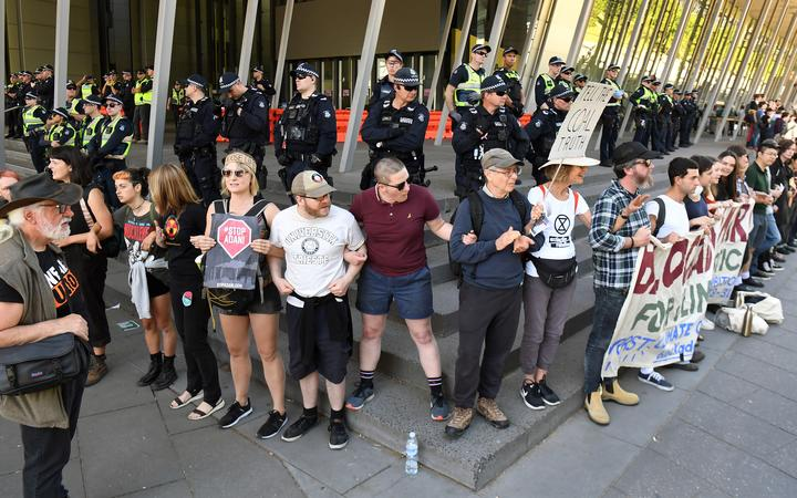 Climate change protesters link arms as they attempt to blockade the International Mining and Resources Conference (IMARC) being held in Melbourne on 29 October, 2019.