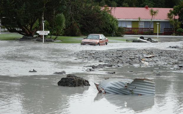 The Waiho River bursts its banks and runs through the Mueller Hotel in Franz Joseph