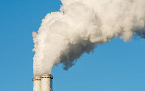 The pipe of a coal power plant with white smoke as a global warming concept.
