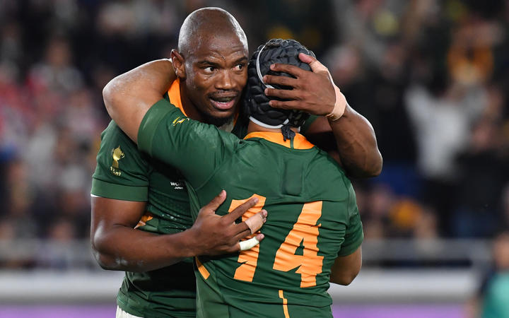 South Africa's wing Makazole Mapimpi is congratulated by South Africa's wing Cheslin Kolbe after scoring his try during the 2019 Rugby World Cup final.