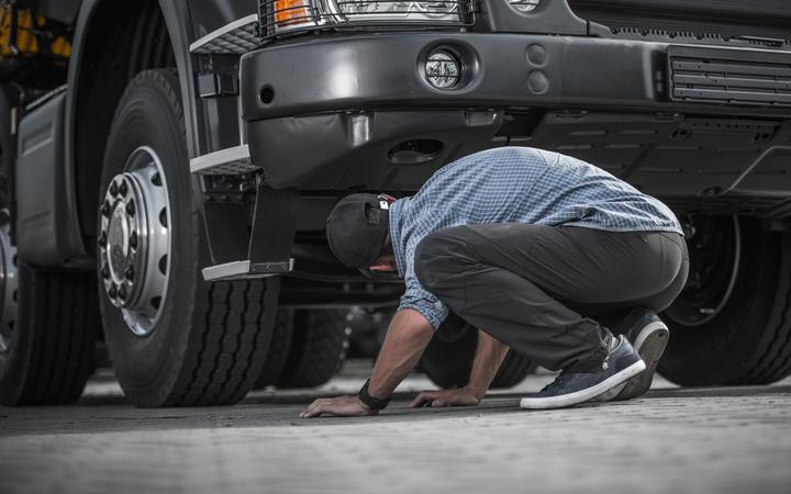 Stock image of someone inspecting a truck.