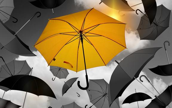 Yellow umbrella seen vividly against background of black umbrellas