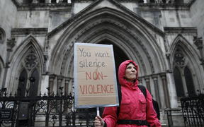 A supporter of climate action group Extinction Rebellion holds a placard outside the Royal Courts of Justice that houses the High Court in London on 24 October, 2019.