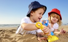Two children wearing hats play with spades on a sunny day at the beach.