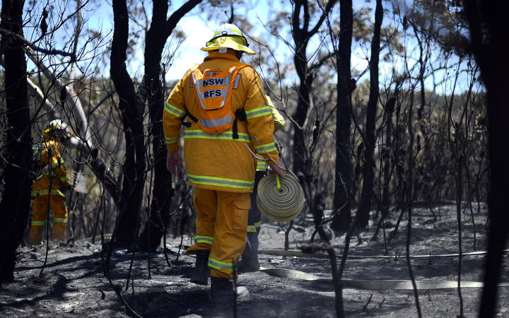 Firefighters monitor bush fires at the Woodford residential area in Blue Mountains on November 12, 2019