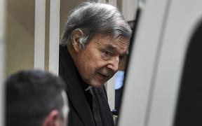 Australian Cardinal George Pell (C) is escorted in handcuffs from the Supreme Court of Victoria in Melbourne on August 21, 2019.
