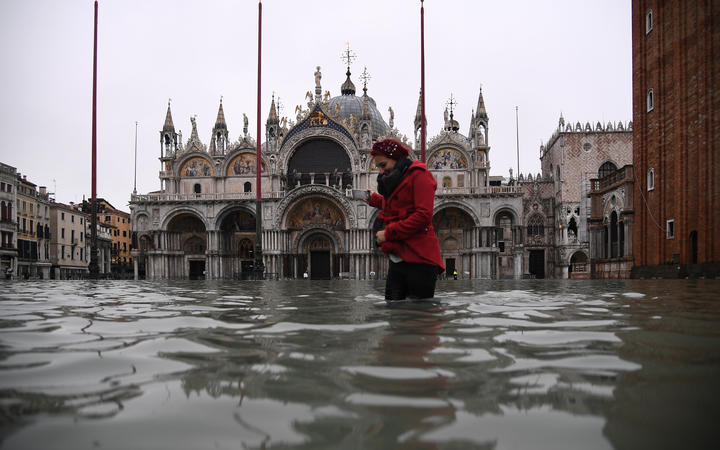 A woman crosses the flooded St. Mark's square by St. Mark's Basilica after an exceptional overnight
