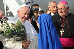 Pope Francis at New York's John F. Kennedy International Airport on September 26, 2015, greeted by nuns from the Monastery of the Precious Blood in Brooklyn, who presented the pontiff with a gift of flowers. Bishop Nicholas DiMarzio (R) of Brooklyn