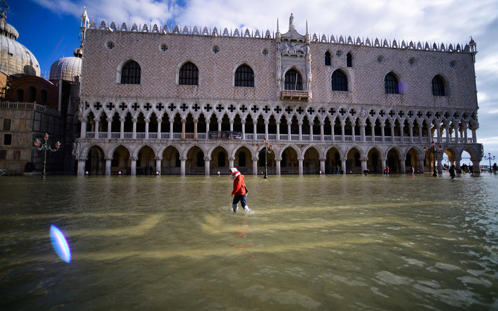 A person walks across the flooded St. Mark's Square by the Doge's palace on 14 November, 2019 in Venice.