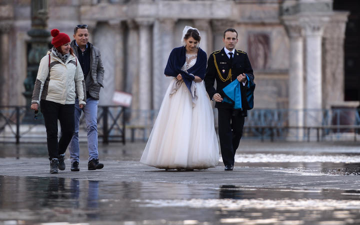 A newlywed couple walks across a flooded square on 14 November, 2019 in Venice.