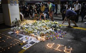 Mourners place flowers and candles as they pay their respects at the car park where student Alex Chow, 22, fell during a recent protest in the Tseung Kwan O area on the Kowloon side of Hong Kong on November 8, 2019.