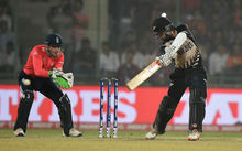 New Zealand's captain Kane Williamson, right, plays a shot as England's wicket keeper Jos Buttler looks on.