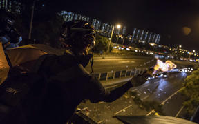 A protester throws a molotov cocktail to stop vehicles from passing through their road block beneath a bridge at the Chinese University of Hong Kong (CUHK) on November 15, 2019.