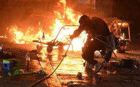 A student tries to extinguish a fire at the entrance of Hong Kong Polytechnic University.