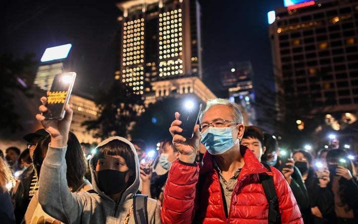 People hold their mobile phones as they gather to pray for the students who are barricaded inside Hong Kong Polytechnic University.