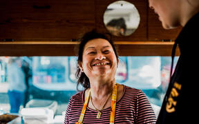 (L-R) Mom Meng glances up at her granddaughter Emrie Meng in her food truck in Lower Hutt, Wellington.