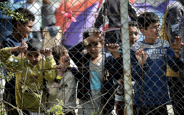 Children stand behind a fence inside the Moria migrant camp transformed in police-run detention facility in Mytilene, on Lesbos island on April 3, 2016.