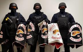 Some members of New South Wales Police's Strike Force Raptor team, with gang members' jackets.