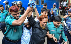 Police escort Islamist extremists who plotted the Holey Artisan Bakery cafe attack to a courtroom for their trial in Dhaka.