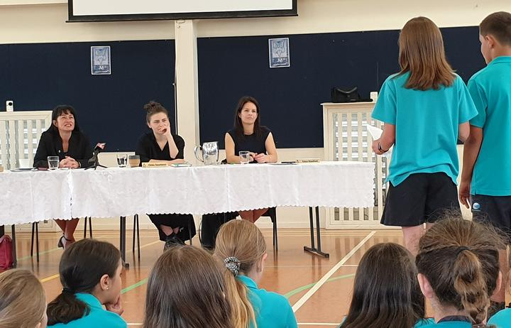 Labour Party MP Marja Lubeck, Green Party MP Chloe Swarbrick and National MP Erica Stanford listen earnestly to Long Bay Primary School year six students' petition.