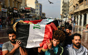 Iraqi mourners carry a coffin, draped in a national flag, of a tuktuk driver who ferried injured protesters and who was later killed in Baghdad.