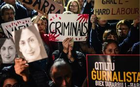People holding placards and photos of killed journalist Daphne Caruana Galizia, stage a protest called by Galizia's family and civic movements, on November 29, 2019 outside the office of the prime minister in Valletta, Malta.
