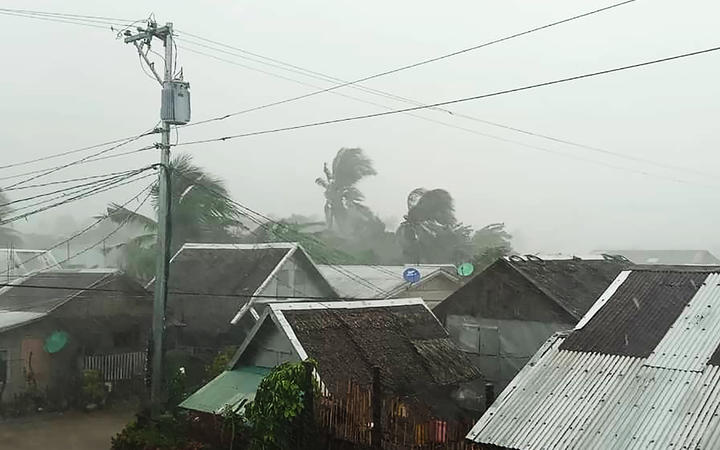 This handout image taken and received on December 2, 2019 courtesy of Gladys Vidal shows heavy rains and moderate wind from Typhoon Kammuri battering houses in Gamay town, Northern Samar province. -