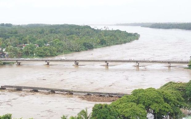 The Sigatoka river rises, with the old bridge in the foreground damaged from previous flooding.