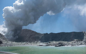This handout photograph courtesy of Michael Schade shows the volcano on New Zealand's White Island spewing steam and ash minutes following an eruption on December 9, 2019.