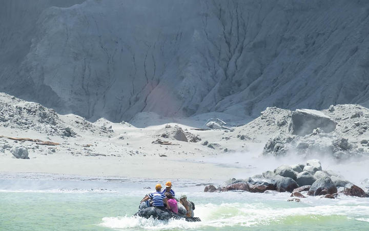 This handout photograph courtesy of Michael Schade shows White Island Tour operators rescuing people minutes after the volcano on New Zealand's White Island erupted on December 9, 2019.