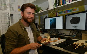 Jacob Blokland pictured with fossils in the Flinders University laboratory.