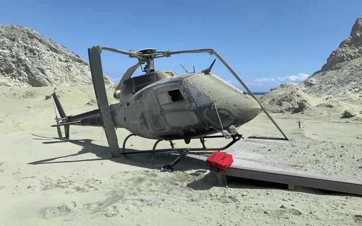 A damaged helicopter is seen on White Island after the eruption.
