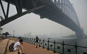 Tourists wearing masks take photos under the Sydney Harbour Bridge enveloped in haze caused by nearby bushfires, in Sydney on December 10, 2019.