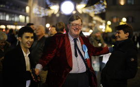 A Conservative Party supporter reacts with delight after the exit poll prediction of a win for PM Boris Johnson's Conservative Party.