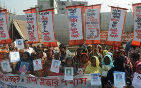 Survivors and relatives of Bangladeshi garment workers killed in the Tazreen Fashions fire accident and Rana Plaza garment factory building collapse react gather for a demonstration in Savar, on the outskirts of Dhaka on November 24, 2013.